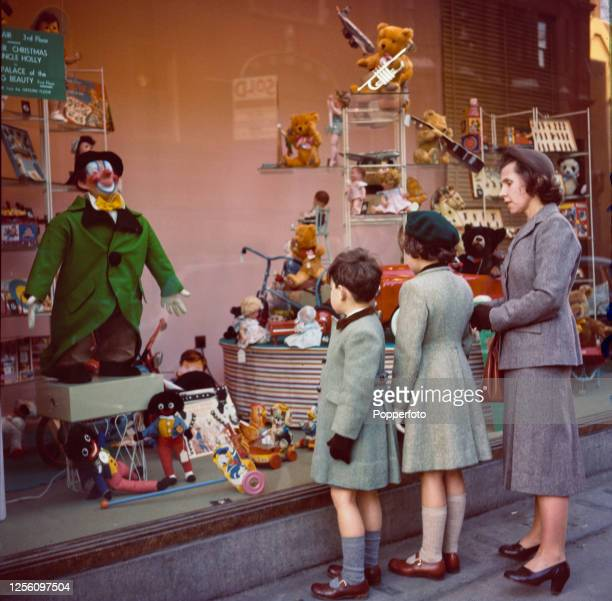 Woman and two children look at the window display of toys, dolls, teddy bears and games at Selfridges department store in Oxford Street, London...