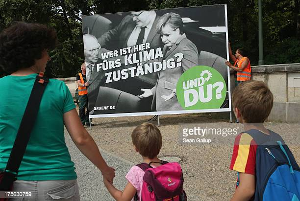 A woman and two children look on as workers set up an election campaign poster of the German Greens Party that shows German Chancellor Angel Merkel...