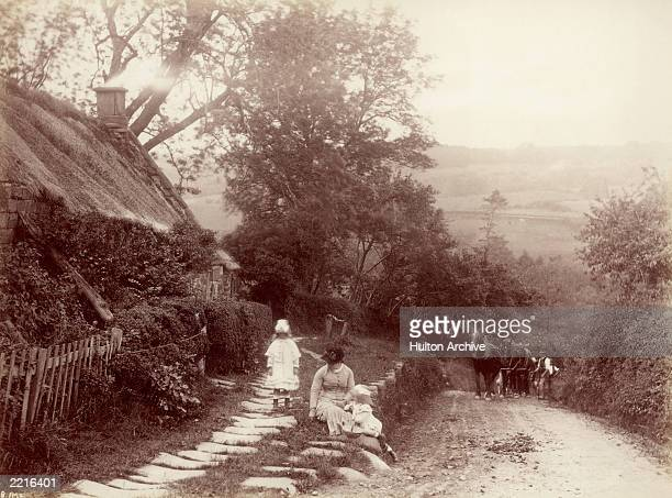 A woman and two children playing by the roadside in Whitby circa 1880