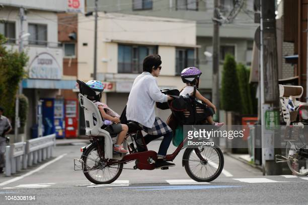 A woman and two children ride on a bicycle across a street in Kawasaki Kanagawa Prefecture Japan on Tuesday Sept 18 2018 Japan's population of 127...