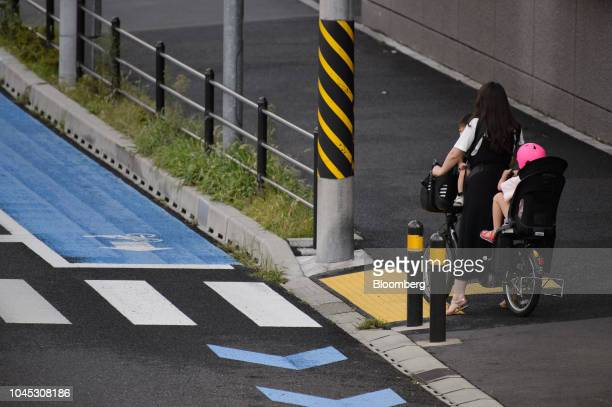 A woman and two children riding on a bicycle wait at a pedestrian crossing in Kawasaki Kanagawa Prefecture Japan on Tuesday Sept 18 2018 Japan's...