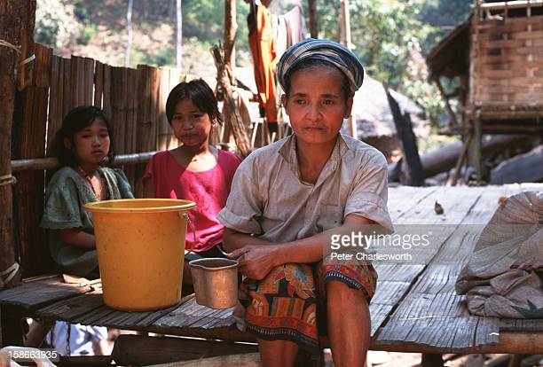 Woman and two children sit on the floor of their wood and bamboo hut in a new Karen refugee camp north of the Thai town, Mae Sot. They are recent...