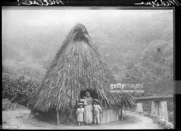 A woman and two children stand at the entrance to a strawroofed hut at the edge of the Metloc gorge near Fortin de las Flores Mexico 1910 The Puente...