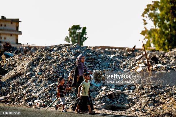 Woman and two children walk past debris in the northern Syrian city of Raqa, the former Syrian capital of the Islamic State group, on August 21,...