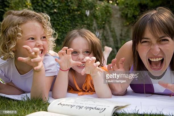 A woman and two girls growling whilst lying down in a backyard