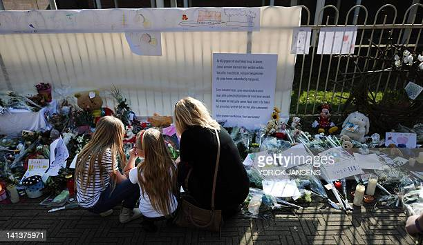 A woman and two girls kneel in front of a tribute to the victims of the March 13 bus crash at the entrance of the primary school 't Stekske in Lommel...