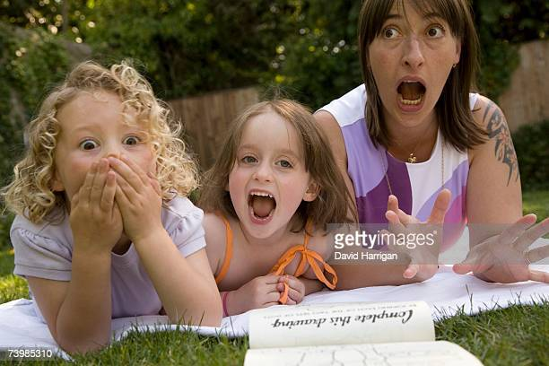A woman and two girls screaming whilst lying down in a backyard