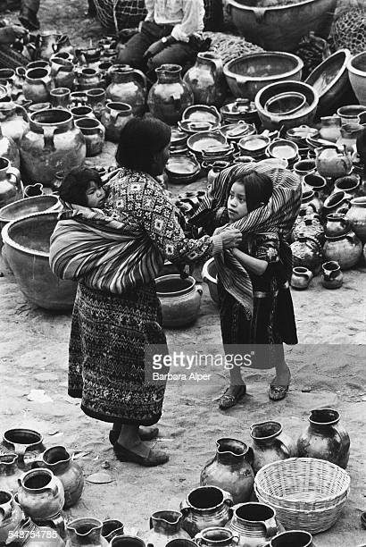 Woman and two girls surrounded by pottery for sale at a market in Chichicastenango, Guatemala, November 1992.