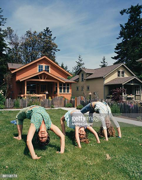 Woman and two girls upside down on lawn