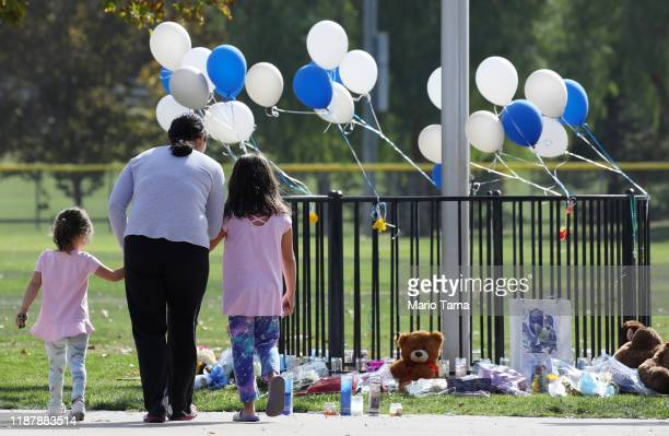 A woman and two girls visit a makeshift memorial in Central Park to victims of the shooting at nearby Saugus High School on November 15 2019 in Santa...