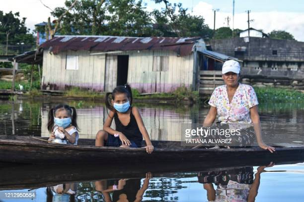 Woman and two girls wearing face masks, as a preventive measure against the spread of the novel coronavirus, COVID-19, sail at the Amazon river in...