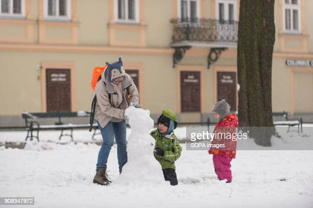 A woman and two kids make a snowman during winter in Krakow