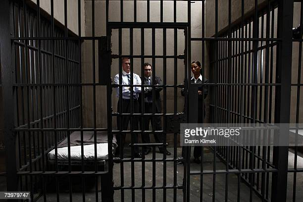 Woman and two men in prison cell, portrait