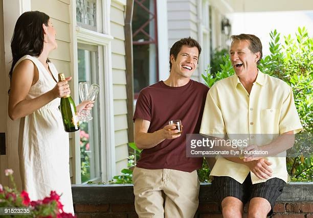 woman and two men on house porch laughing