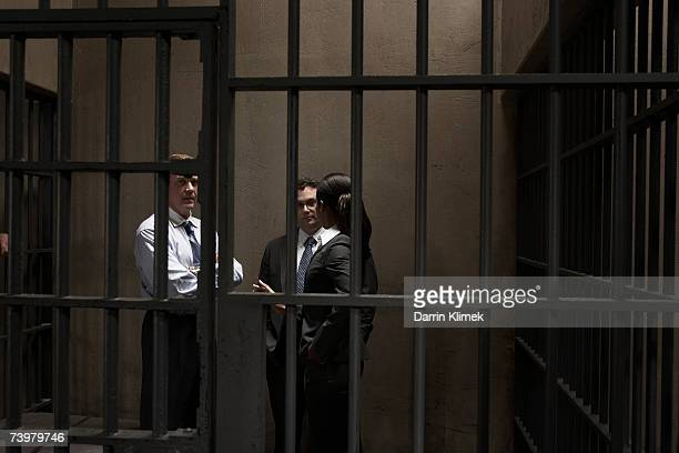 Woman and two men talking in prison cell