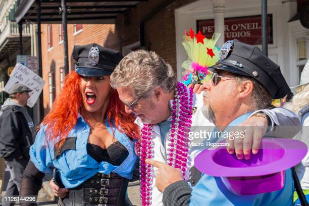 a woman and two men wearing police costumes and having fun in the street during the mardi gras celebration at new orleans carnival, louisiana, usa. - mardi gras fun in new orleans stock photos and pictures