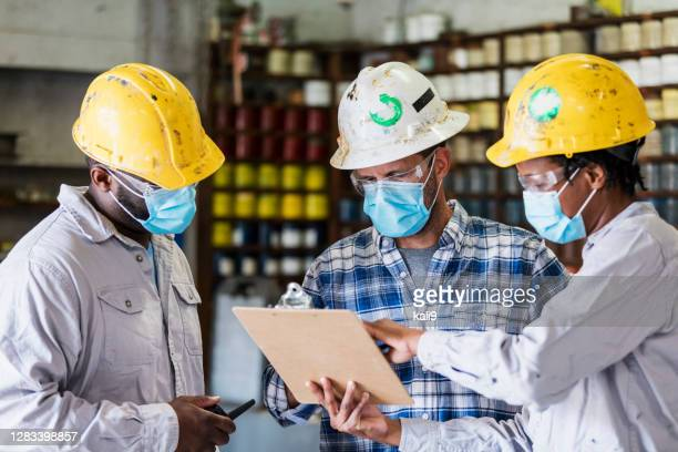 woman and two men working in factory wearing masks - essential services stock pictures, royalty-free photos & images
