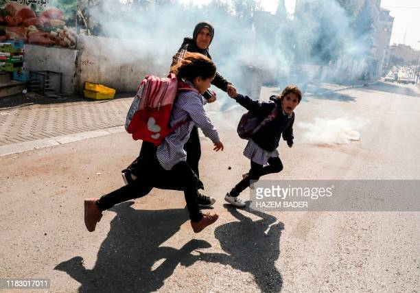 TOPSHOT A woman and two school girls attempt to flee from tear gas fired at Palestinian journalists gathering for a demonstration by Israel's...