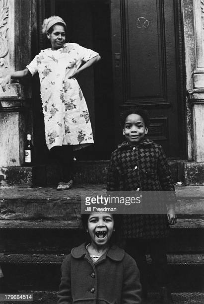 A woman and two young girls pose on the steps of an apartment block in Lower Manhattan New York City 1966