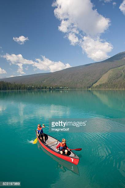 woman and young boy canoeing on beautiful mountain lake - paddling stock pictures, royalty-free photos & images