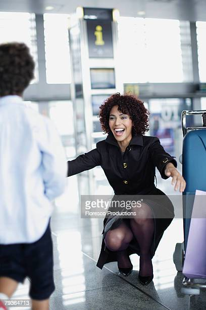 Woman and young boy in airport reuniting