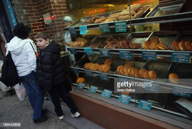 A woman and young boy prepare to buy pastries at a bakery in the city center on March 7 2013 in Bucharest Romania Both Romania and Bulgaria have been...