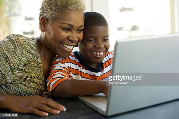Mujer y joven niño sentado en la computadora portátil