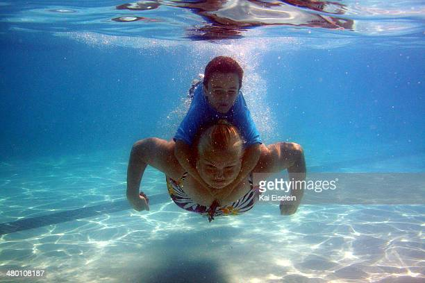 CONTENT] A woman and young boy swim underwater in a pool