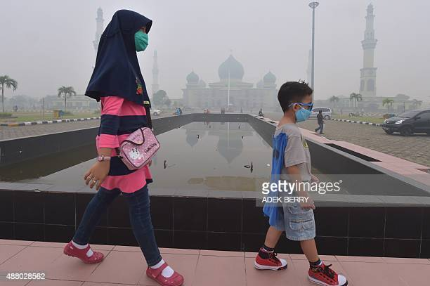 A woman and young boy walk past the AnNur Great Mosque as haze shrouds the Sumatran city of Pekanbaru in Riau province on September 13 2015 Smog from...