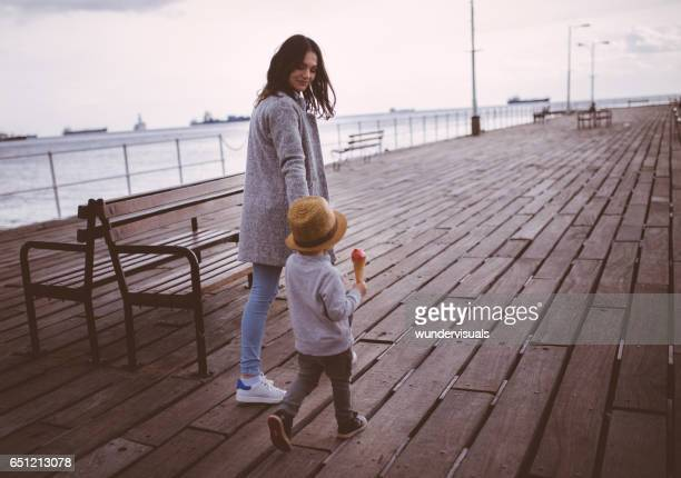 Woman and young boy walking on a pier