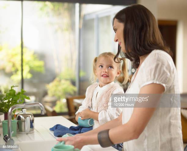 Woman and young daughter washing up together