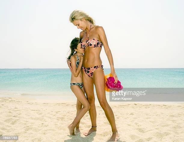 woman and young girl at the beach smiling. - indian bikini stock pictures, royalty-free photos & images