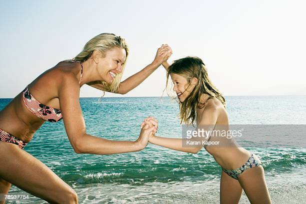Woman and young girl being playful at the beach smiling.