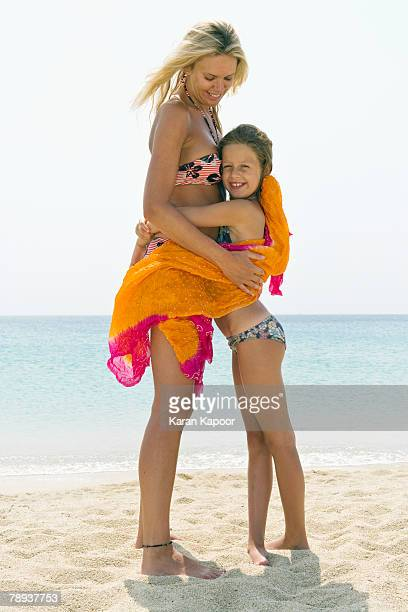 woman and young girl embracing at the beach smiling. - indian bikini stock pictures, royalty-free photos & images