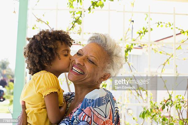 woman and young girl embracing outdoors - actieve ouderen stockfoto's en -beelden