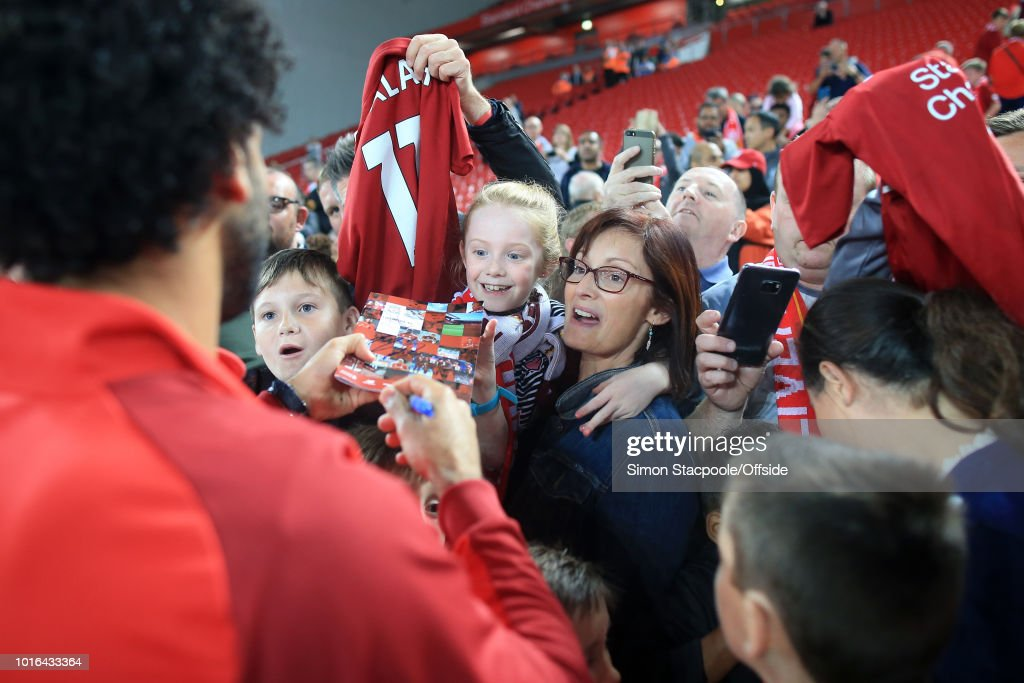 A woman and young girl get an autograph from Mohamed Salah of Liverpool after the pre-season friendly match between Liverpool and Torino at Anfield on August 7, 2018 in Liverpool, England.