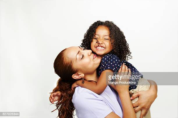 woman and young girl hugging and kissing - mãe - fotografias e filmes do acervo
