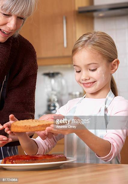 Woman and young girl in kitchen putting a layer cake together and smiling