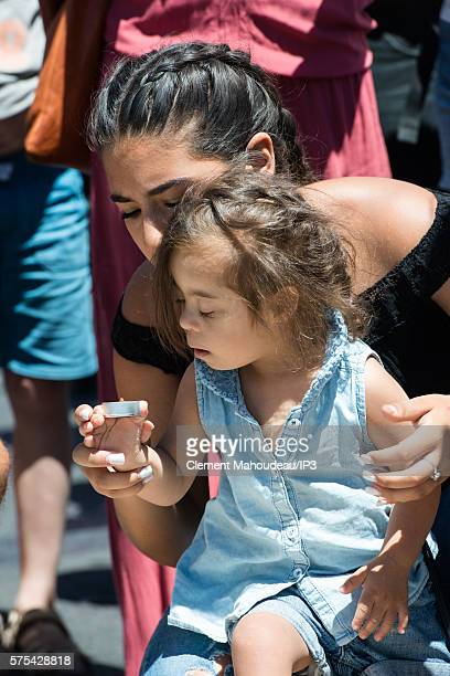A woman and young girl leave tributes on La Promenade des Anglais' seafront for the victims of yesterday's attack on July 15 in Nice France A...