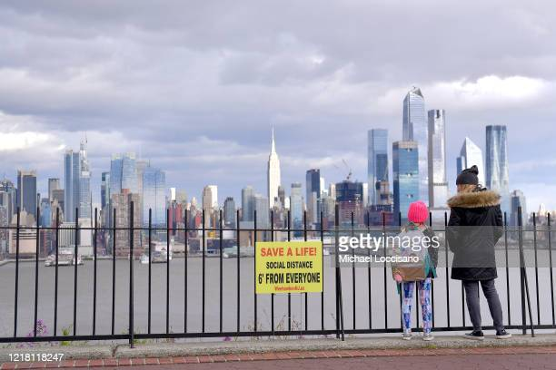A woman and young girl look at the view of Manhattan standing next to one of many social distance signs recently posted on fences April 10 2020 in...