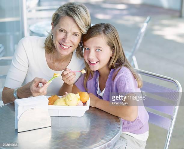 Frau und junge Mädchen auf der Terrasse im Freien essen Eis