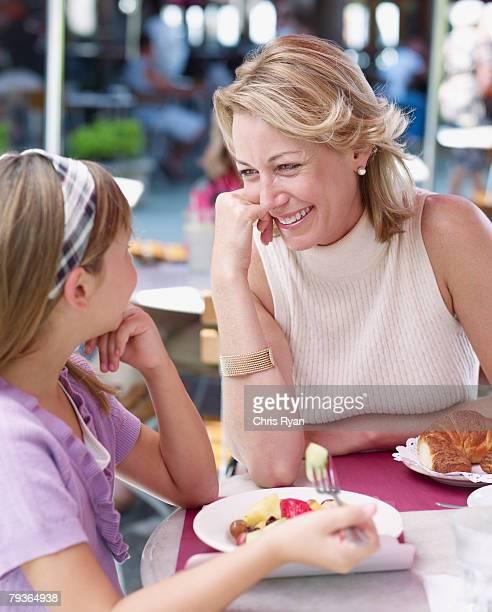 Femme et jeune fille mangeant repas sur le patio extérieur