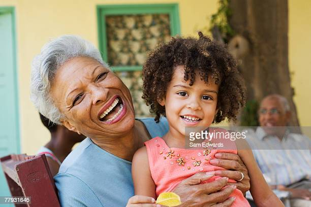 woman and young girl outdoors with people in background - grandmother stock pictures, royalty-free photos & images