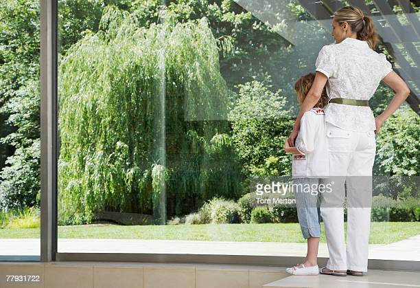 Woman and young girl standing in front of large window