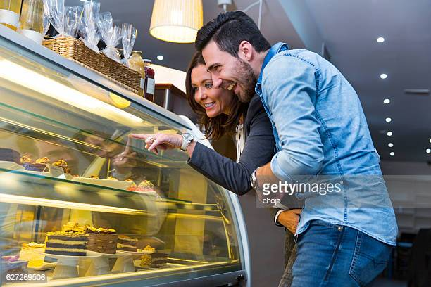 Woman and young man looking at display window with cakes
