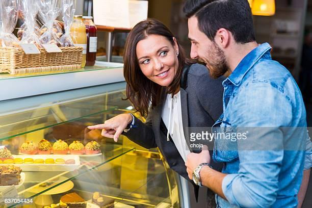 Femme et jeune homme regardant afficher la fenêtre avec des gâteaux