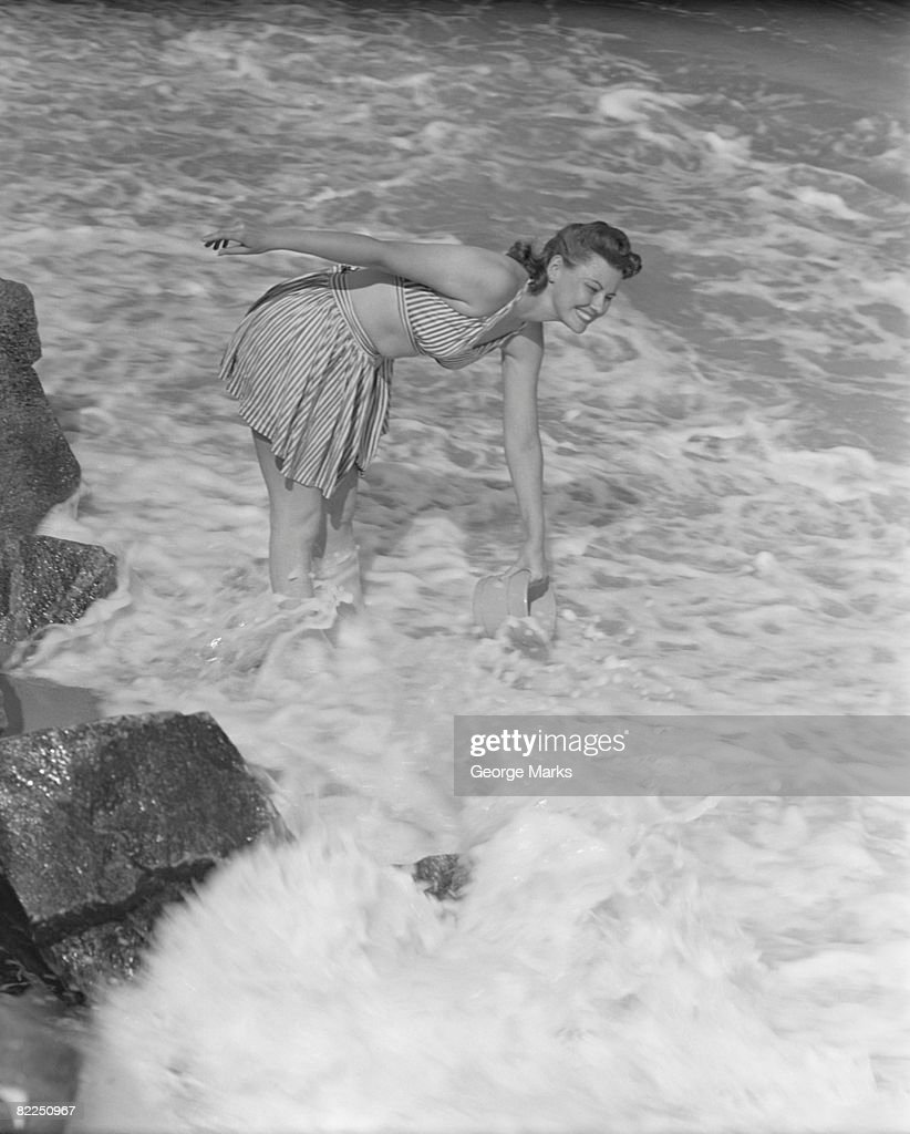 Woman ankle deep in sea : Stock Photo