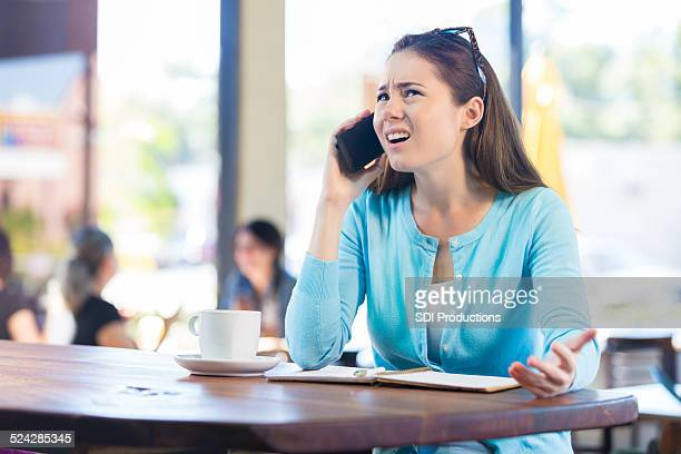 Woman annoyed by phone call in local coffee shop