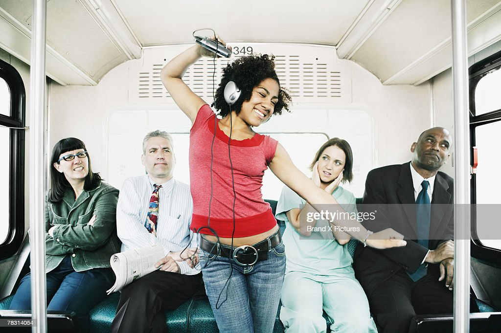 Woman annoying passengers by dancing on bus : Stock Photo