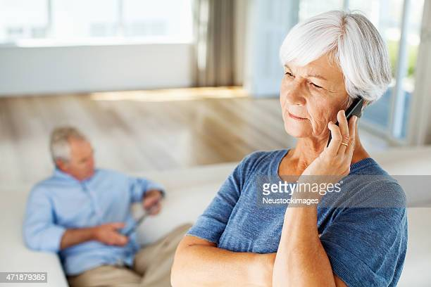 Woman Answering Smart Phone At Home